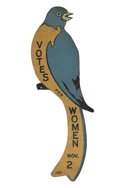 "Image of a tin sign in the shape of a bluebird with yellow belly that reads ""Votes for Women"" Nov. 2"